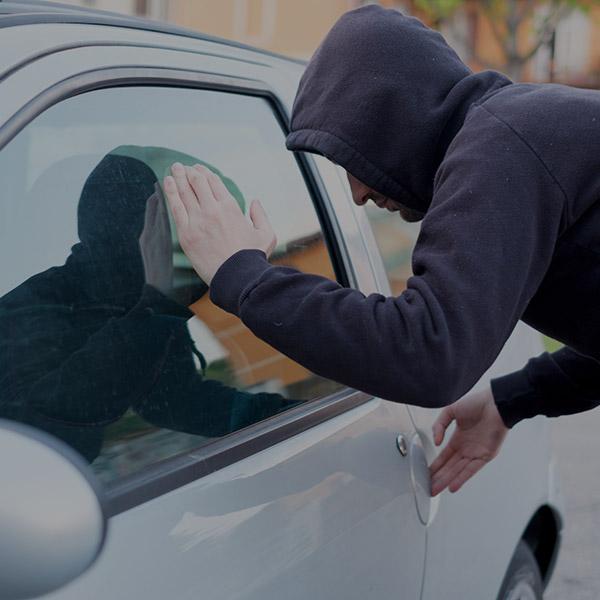 Man looking through car window suspiciously